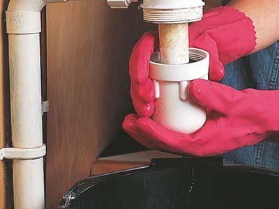 Plombier débouche un siphon d'évier