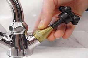 Plombier qui procède à une vérification siège robinet dans le cadre d'une réparation de fuite